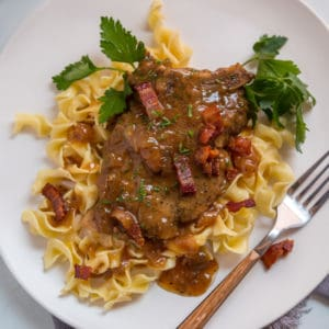 Instant Pot pork chops with egg noodles and fresh parsley on a white plate with a wooden handled fork