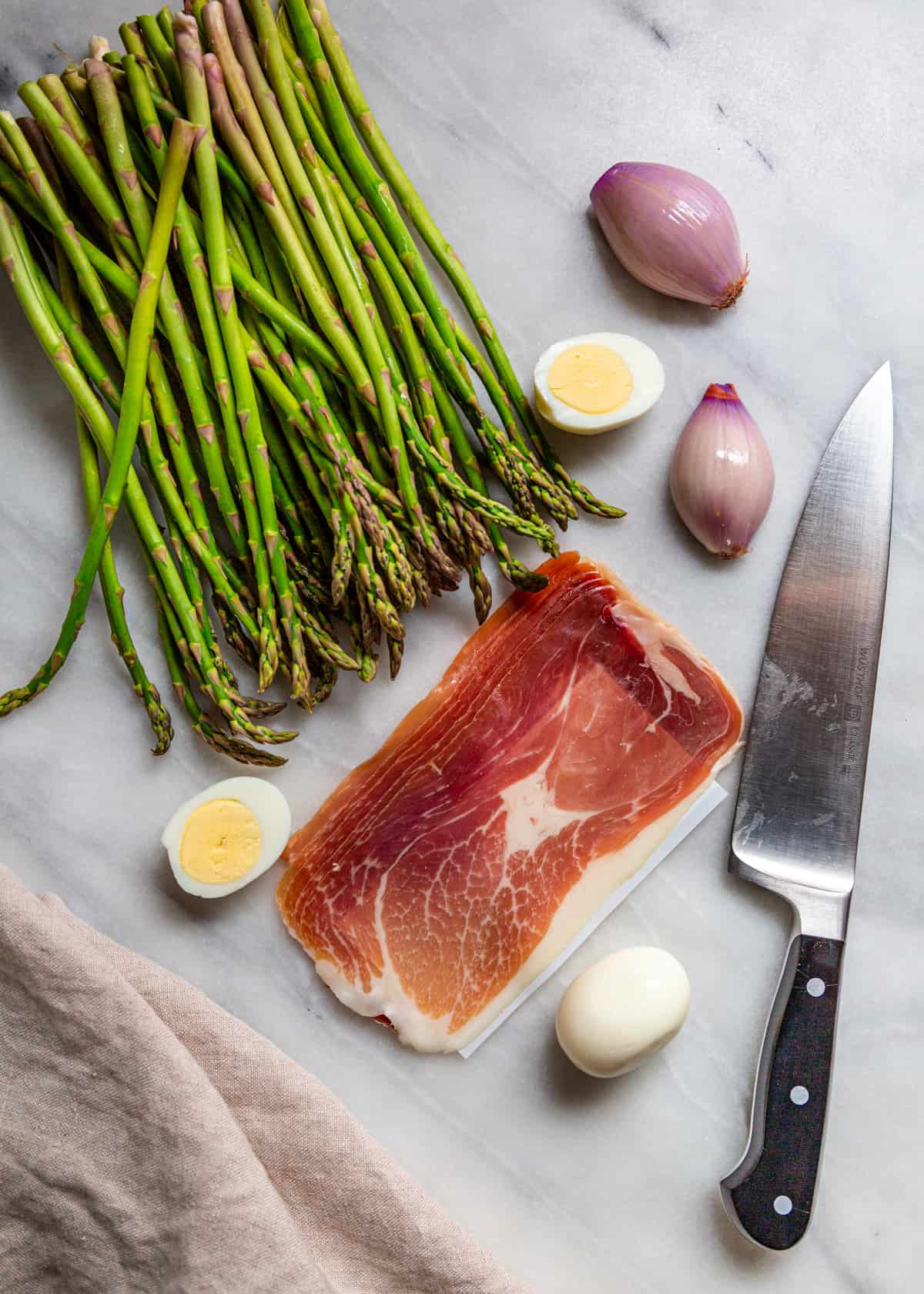 raw stalks of green vegetable, prosciutto, eggs and shallots on marble top counter with a chef's knife