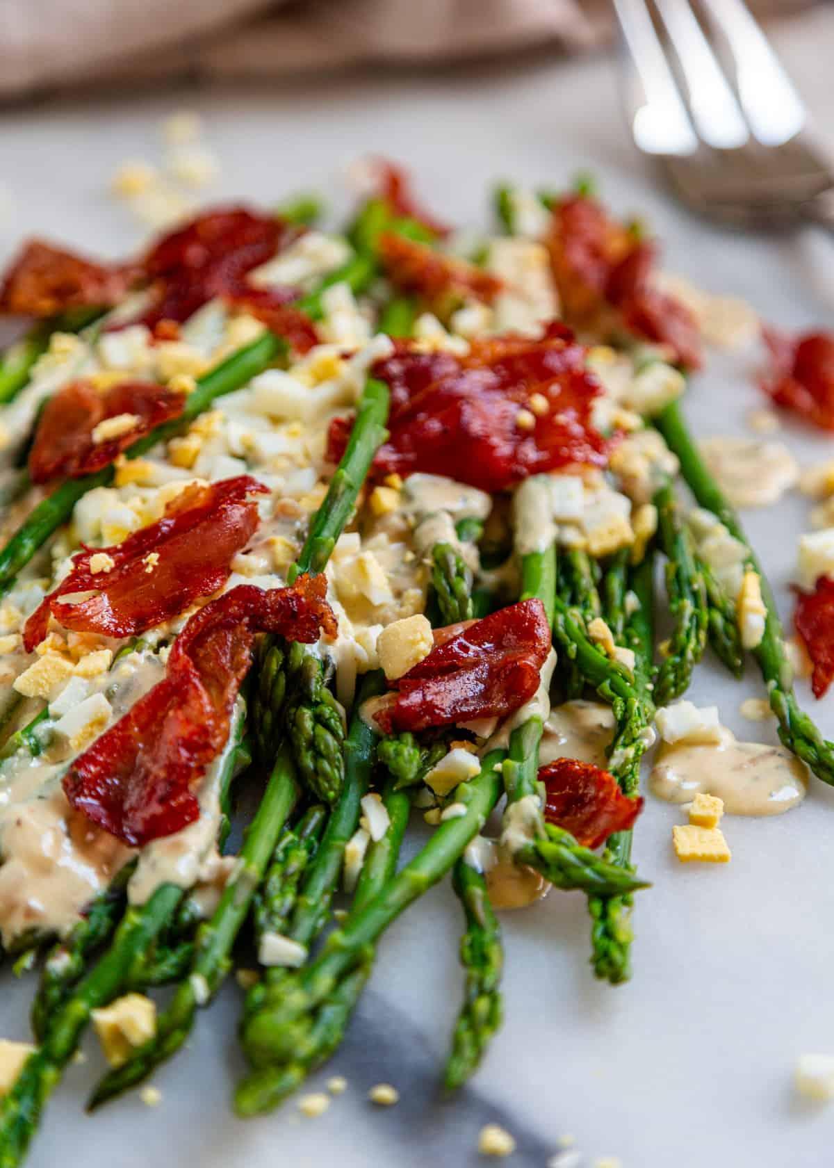crispy prosciutto crumbled on asparagus with tarragon sauce