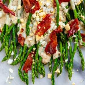 crispy prosciutto crumbled on asparagus with chopped egg and tarragon sauce