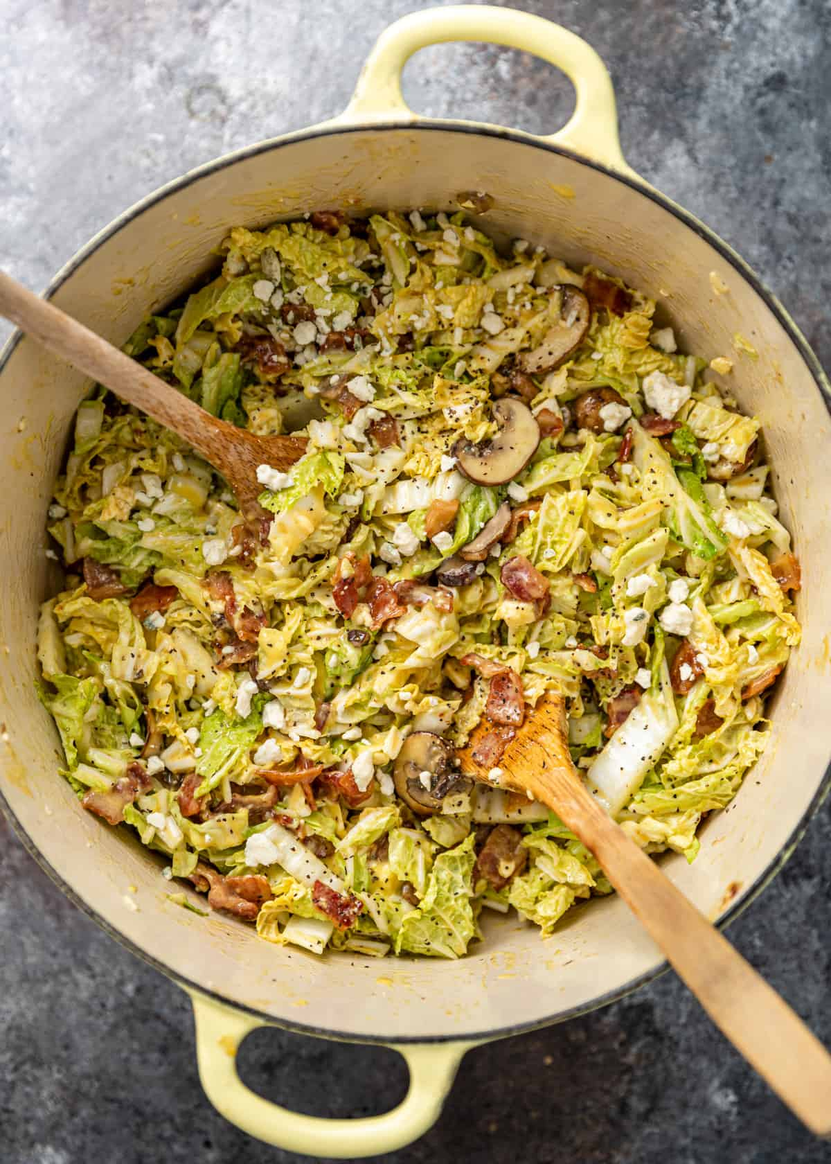 warm napa cabbage salad in dutch oven with two wooden spoons