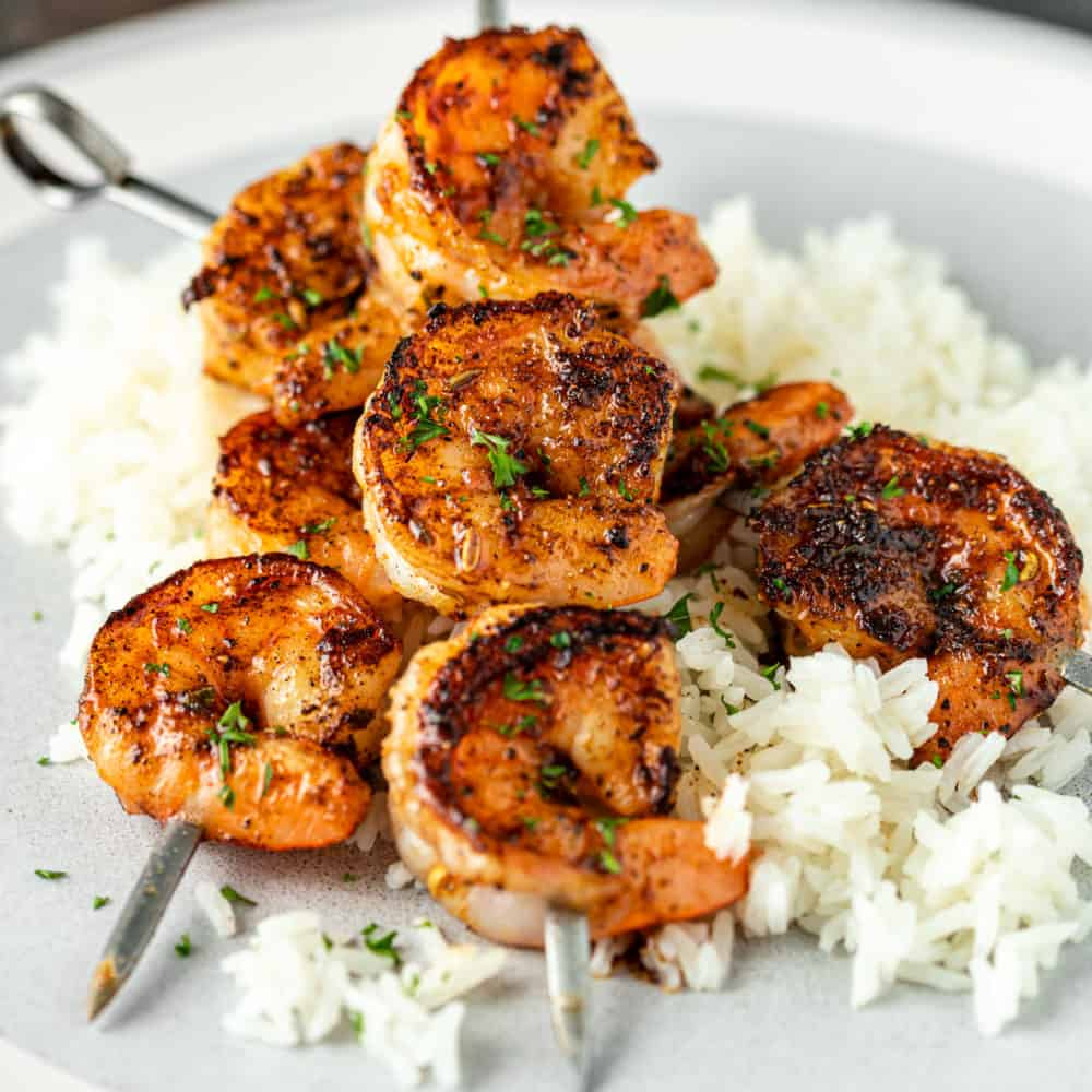 skewers of perfectly blackened shrimp on bed of fluffy white rice