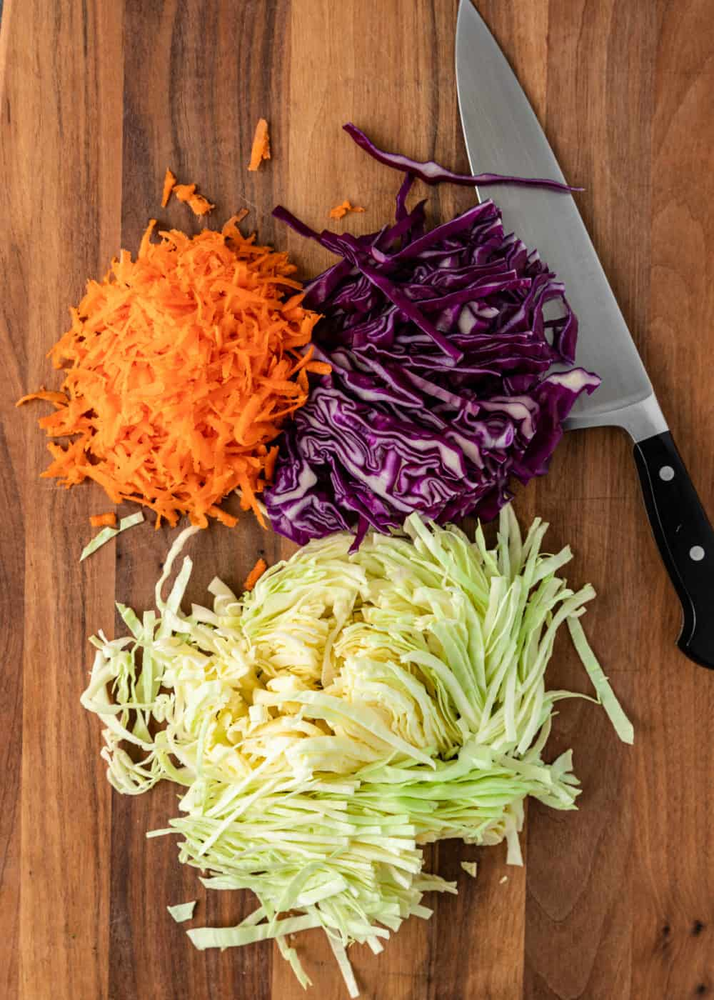 overhead photo: piles of shredded white cabbage, purple cabbage, and carrots on cutting board next to chef's knife