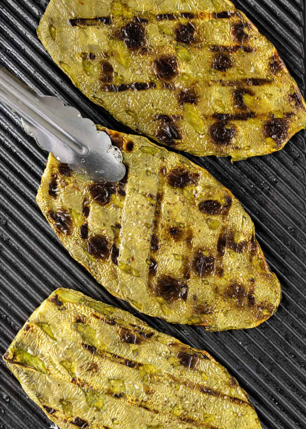 overhead image: 3 cactus paddles on a grill, one being turned with metal tongs