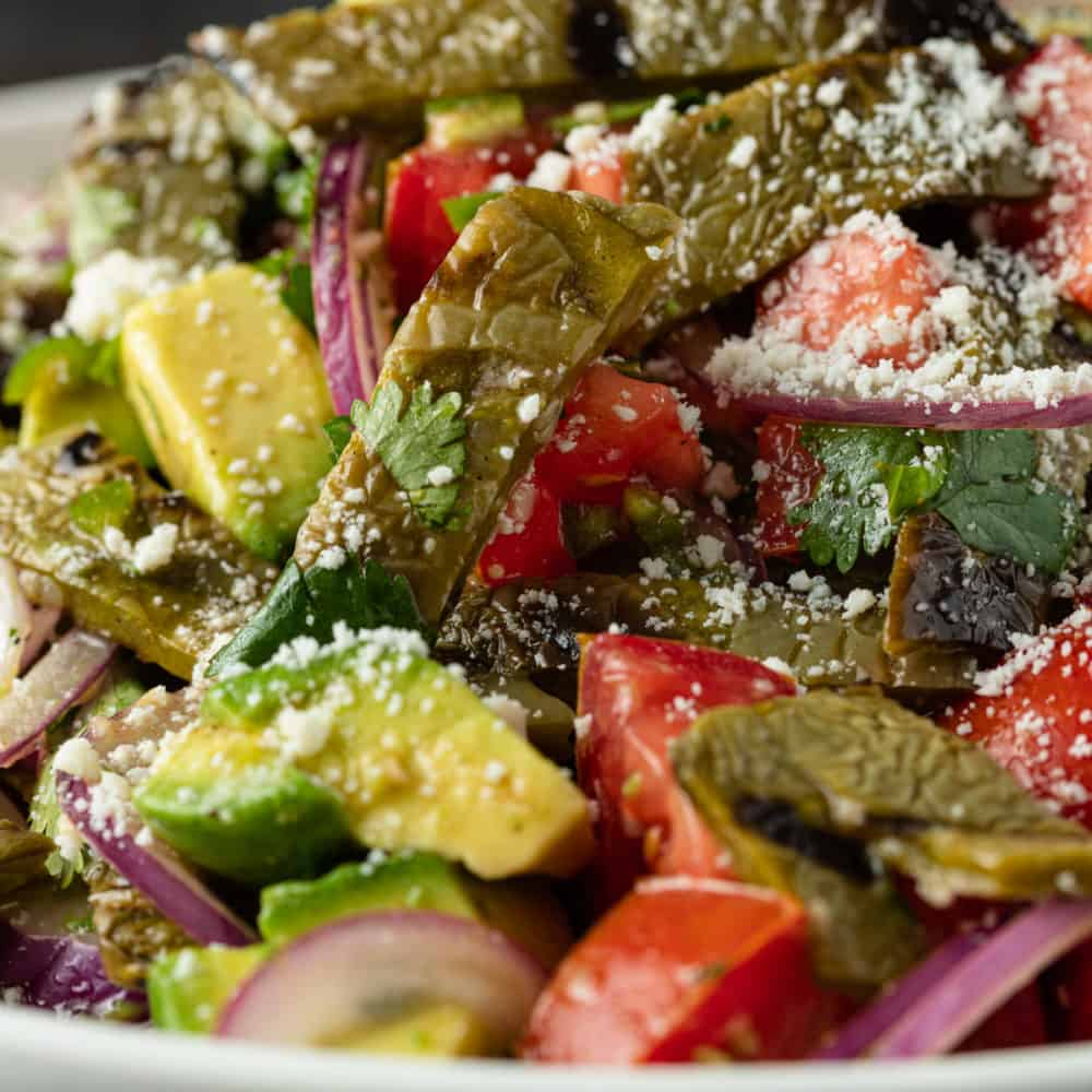 close up image of chopped avocado, tomatoes, red onion, and cactus paddles with crumbled Cojita on top