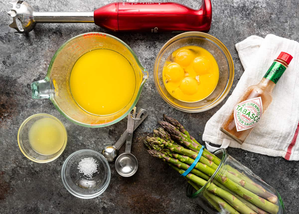 overhead photo: easy hollandaise sauce recipe ingredients in measuring cups next to bunch of fresh asparagus