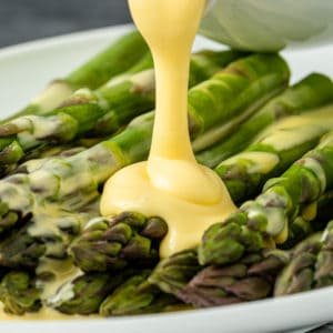 A plate of asparagus with hollandaise drizzled on top