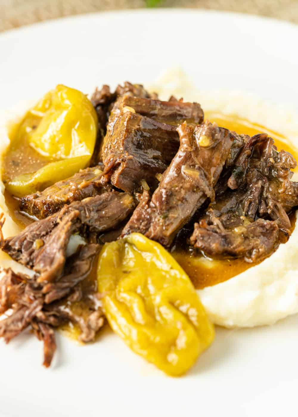 tender shredded chunks of beef chuck and pepperoncinis on mashed potatoes