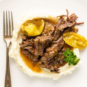 close up of Instant Pot Mississippi Roast on plate with mashed potatoes