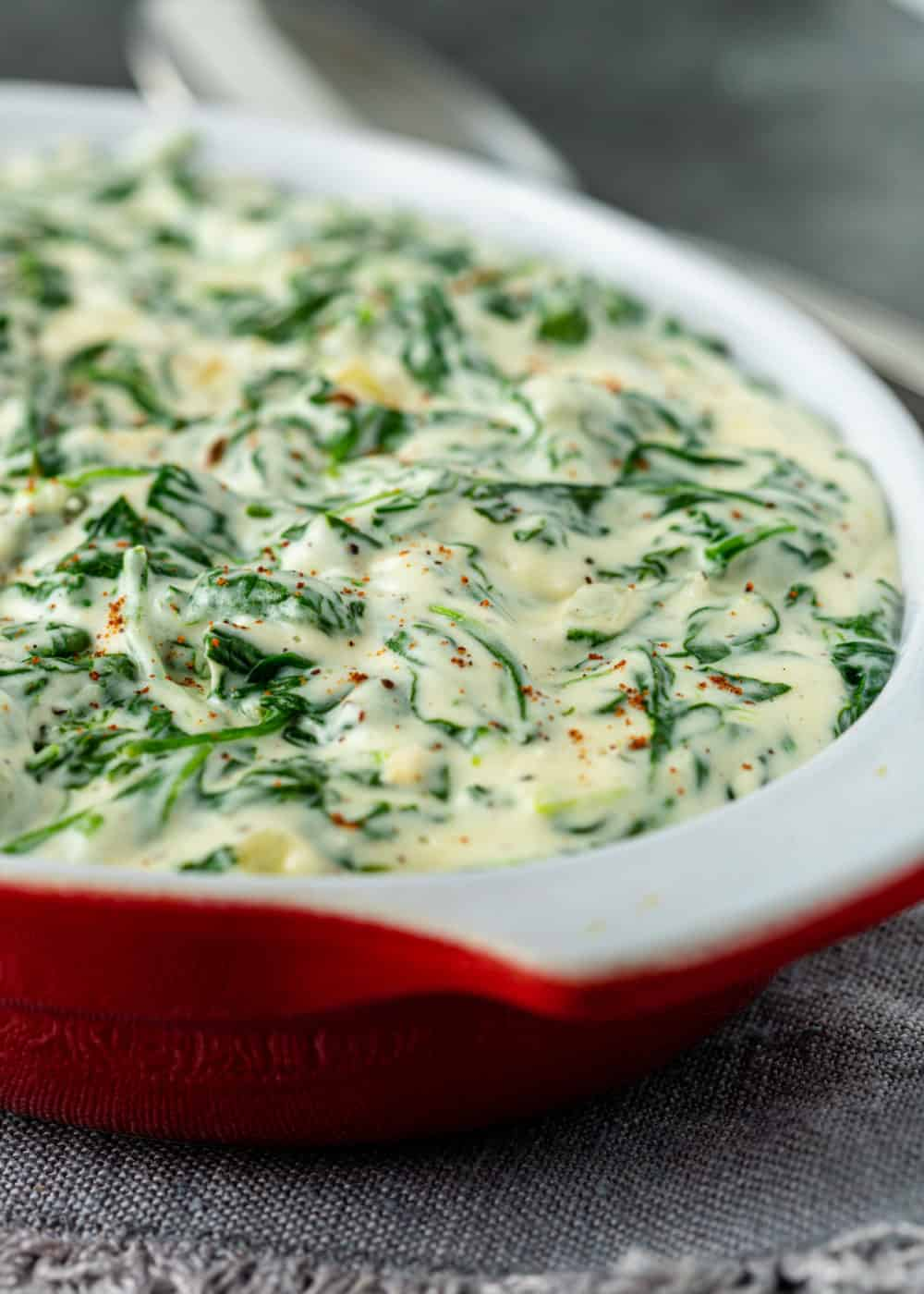closeup photo of cooked spinach in creamy white sauce