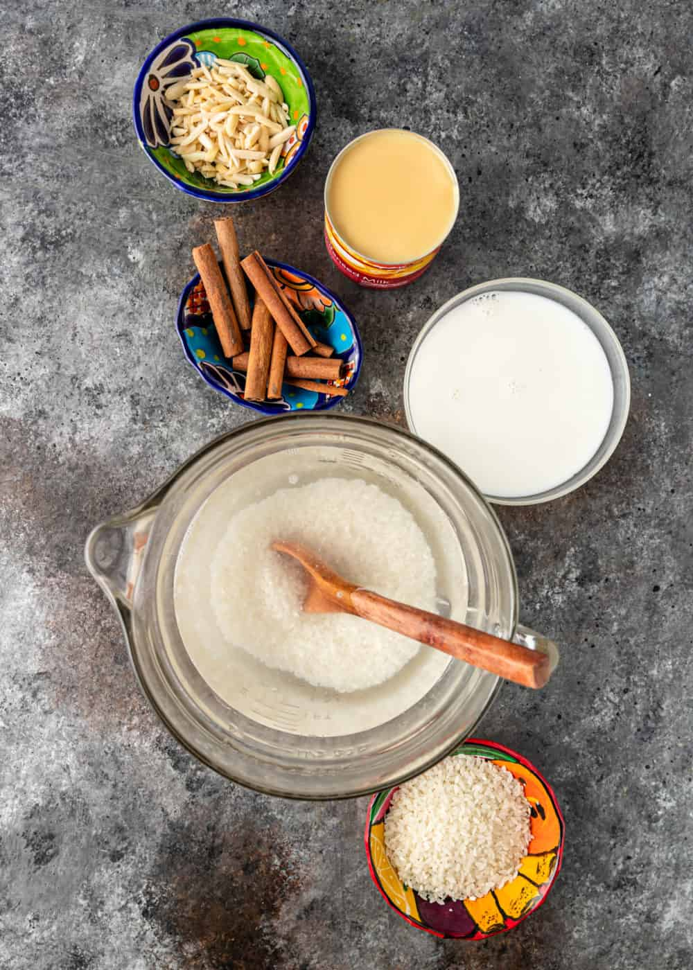 overhead: ingredients in small bowls and liquid measuring cups to make a horchata recipe