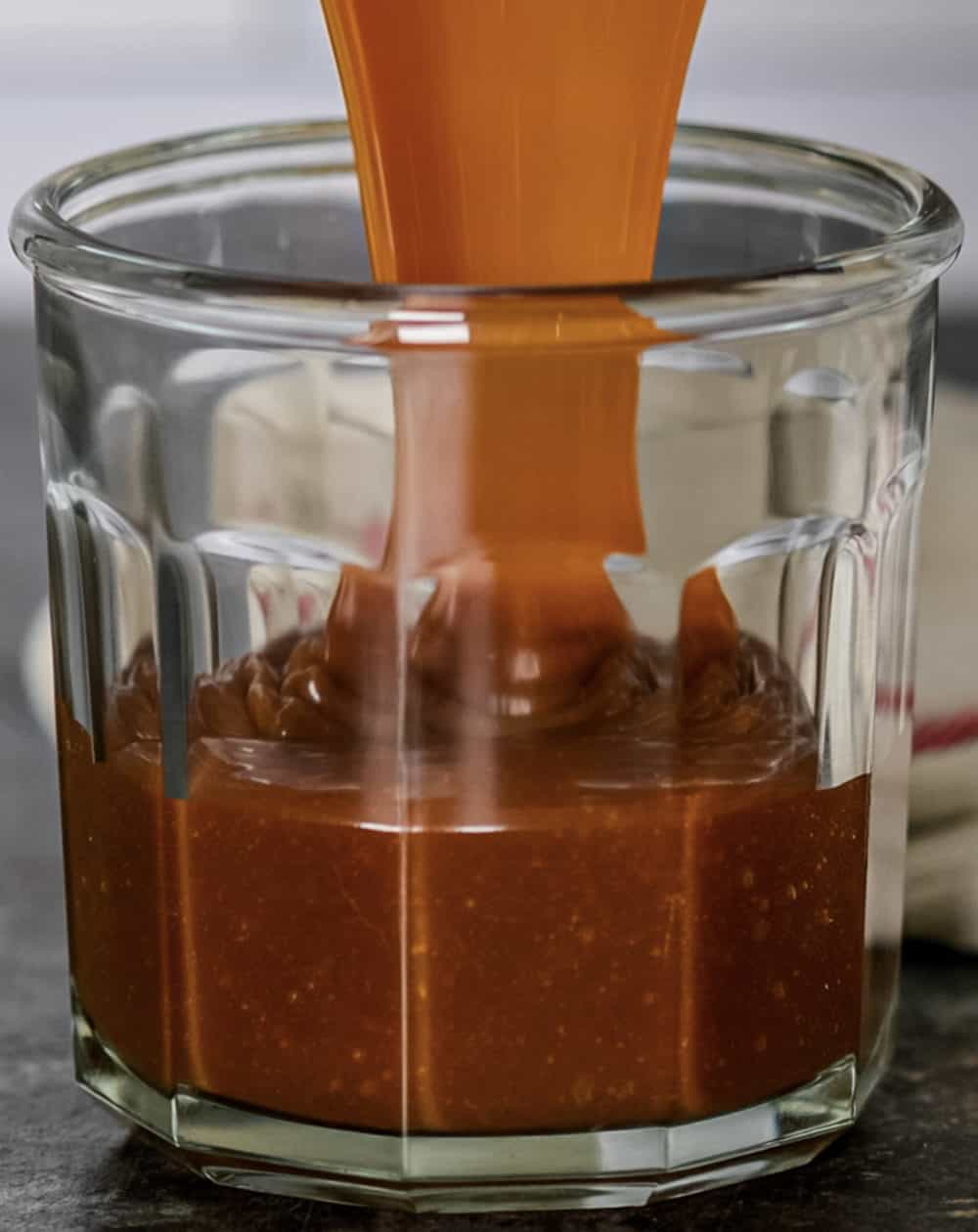 caramel being poured into a glass container