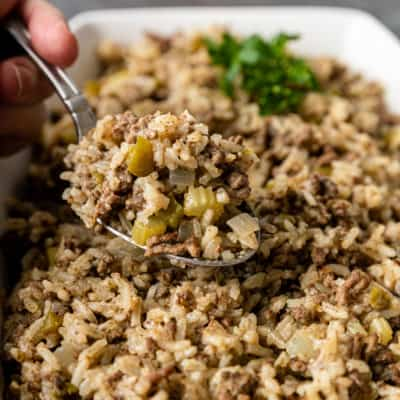 spoonful of a Cajun beef and rice side dish above the serving bowl
