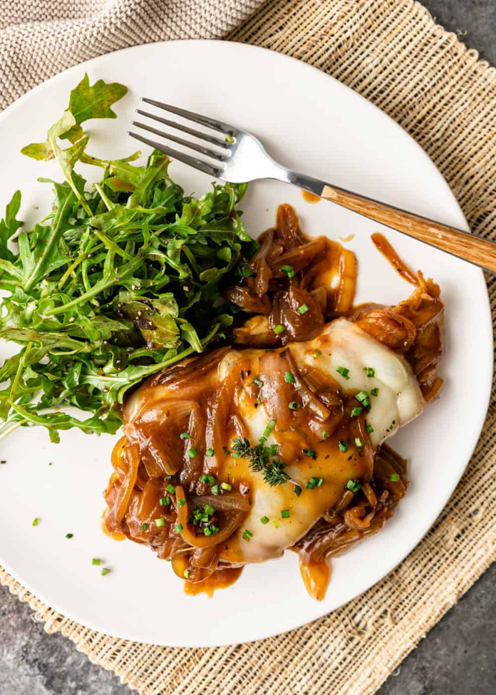 chicken with onions, sauce, and greens with a fork on a white plate
