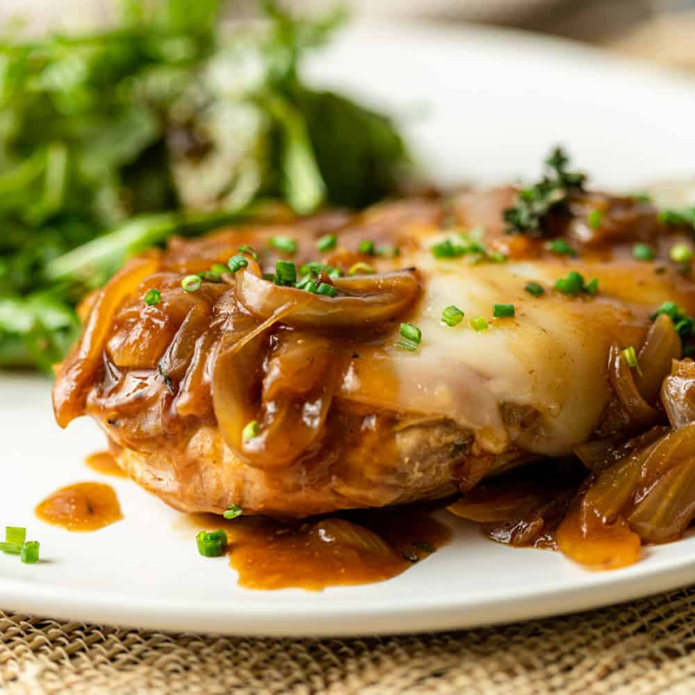french onion chicken with garnish on a plate