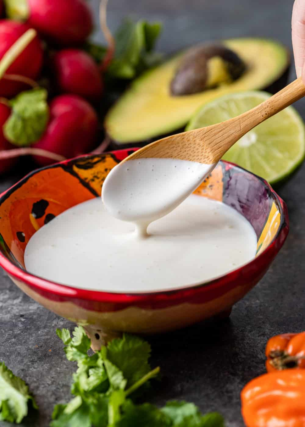 small wooden spoon in bowl of Mexican crema