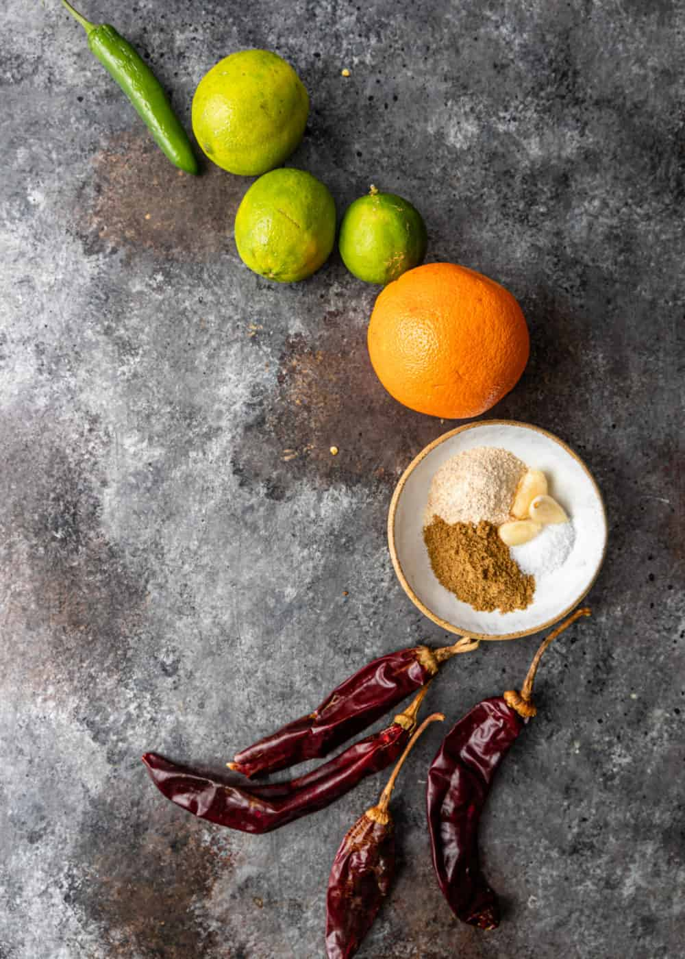 overhead: oranges, limes, chiles and spices for making carne asada marinade