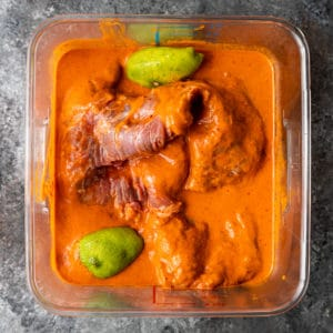 overhead: carne asada meat in square container of carne asada marinade