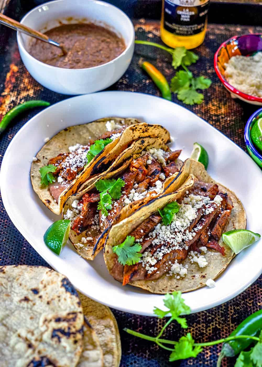 Mexican steak taco dinner on table with corn tortillas and refried beans