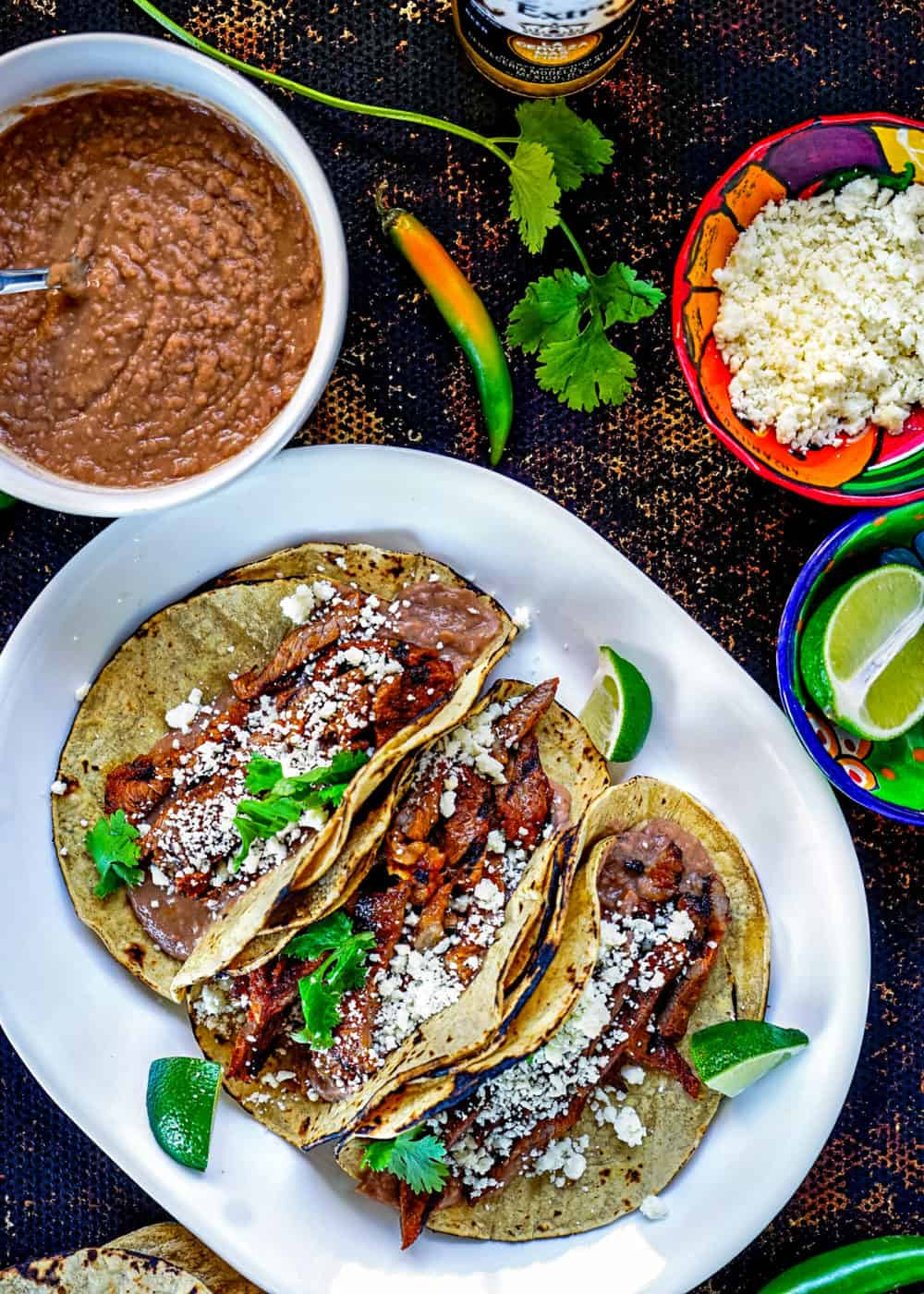 overhead: Mexican marinated steak in corn tortilla shells on platter next to bowls of refried beans, lime wedges and crumbled cojita