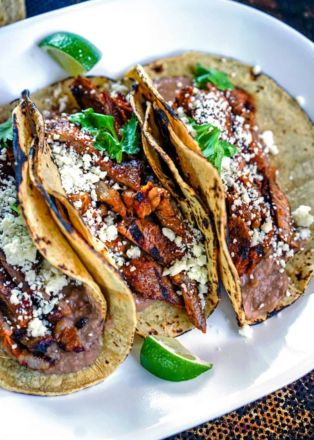 overhead: platter of flank steak tacos garnished with cojita cheese and cilantro