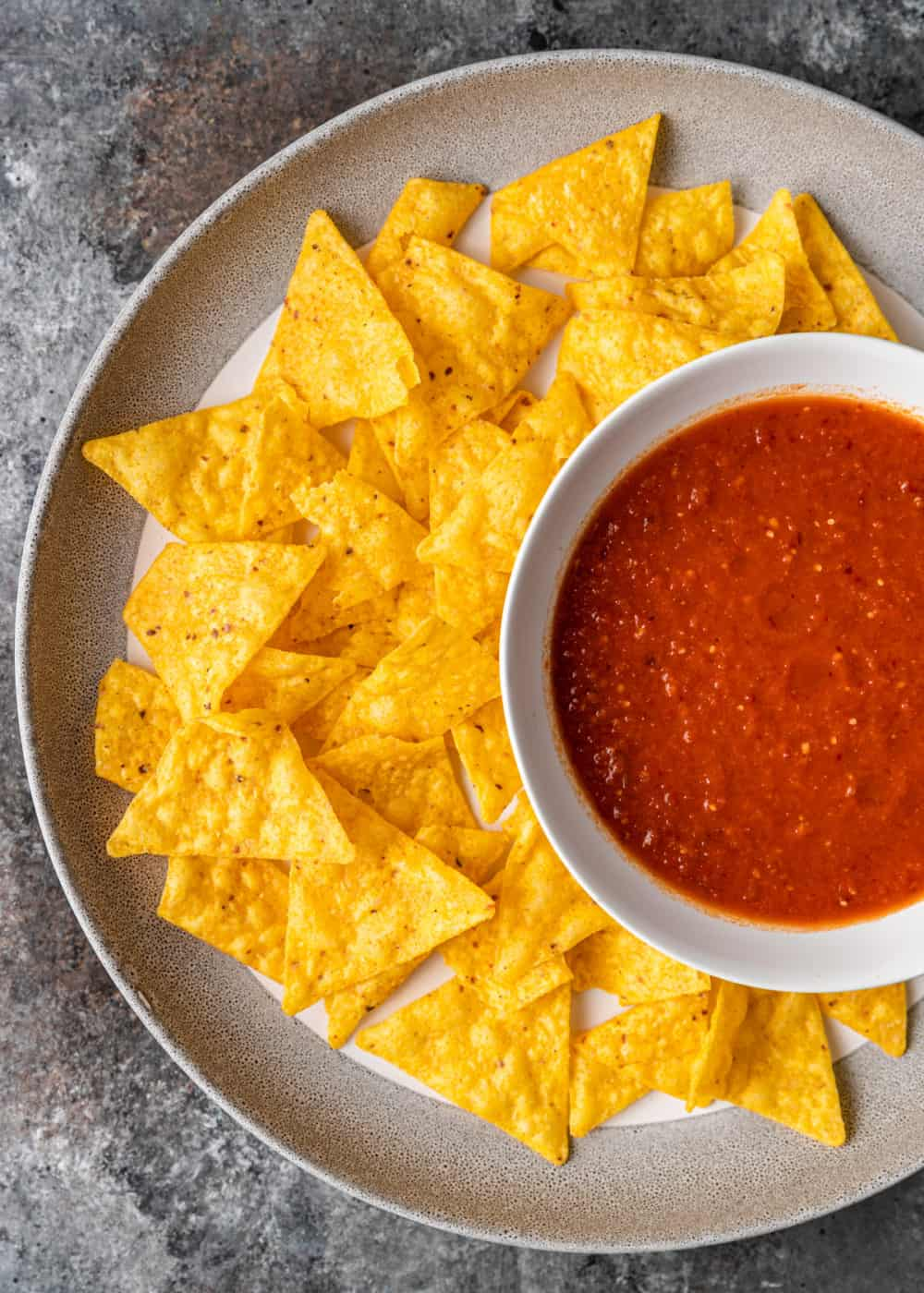 overhead photo of tortilla chips on platter with spicy red dip
