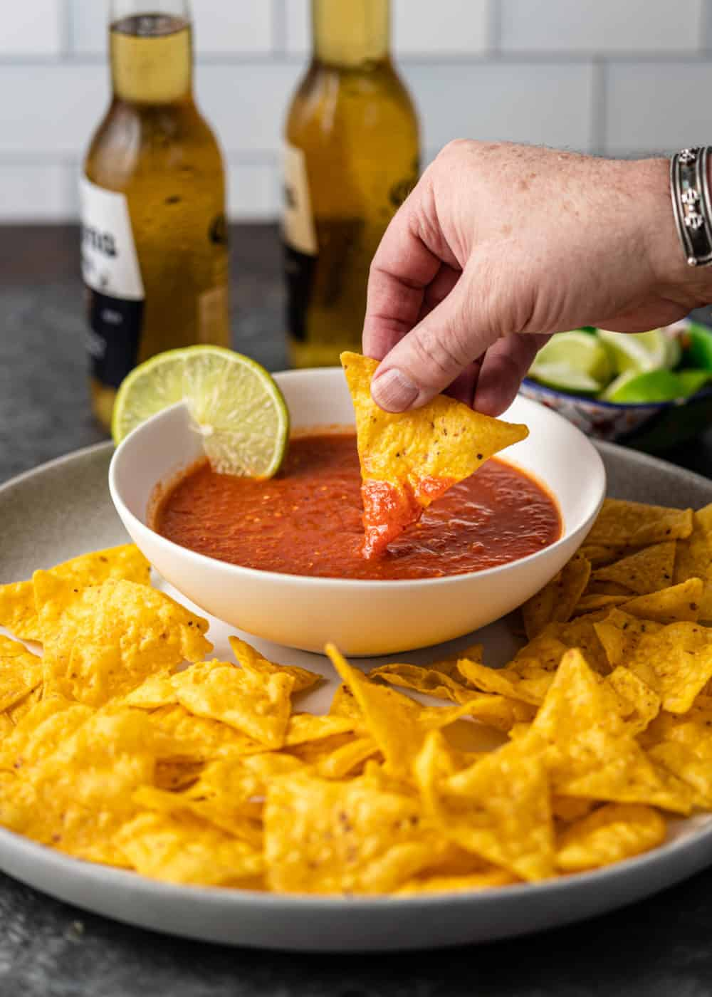 bowl of chile de arbol salsa in white bowl on platter with corn tortilla chiips