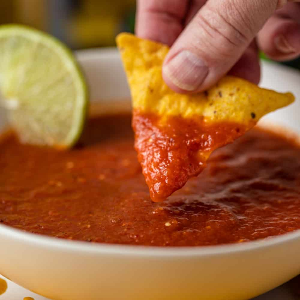 side view close up: dipping yellow corn chip into bowl of red tomato and tomatillo salsa
