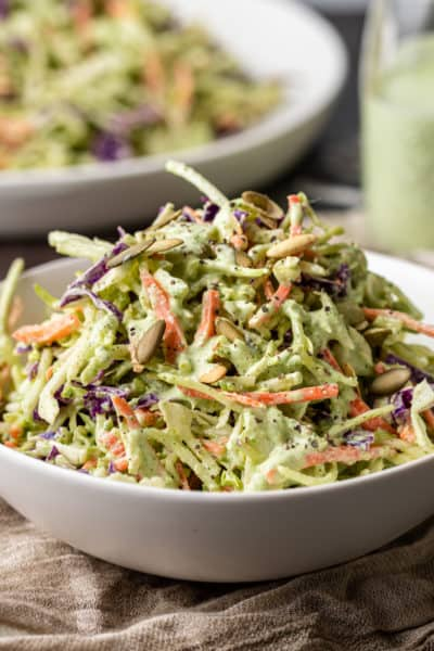 side view: creamy cilantro dressing tossed with shredded green and purple cabbage and carrots