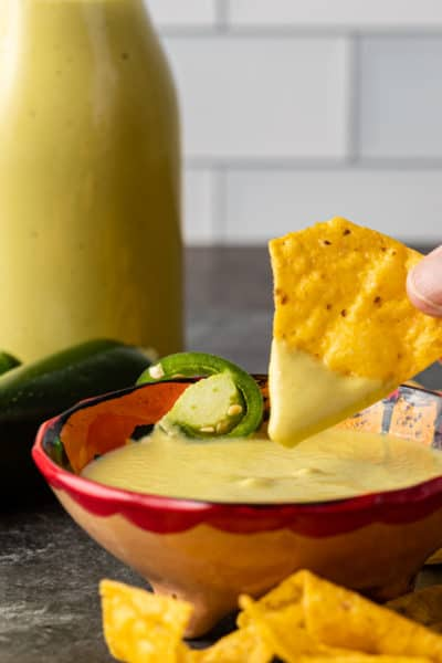 dipping yellow corn tortilla chip into bowl of creamy jalapeno dip