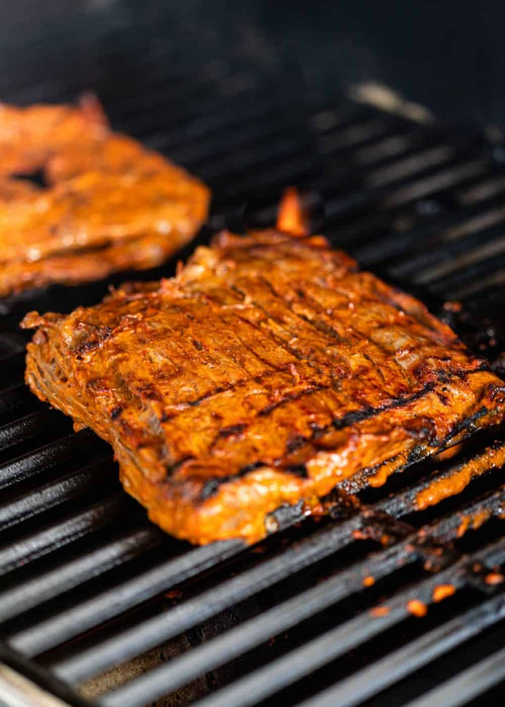 close up: cooking carne asada steak on grill