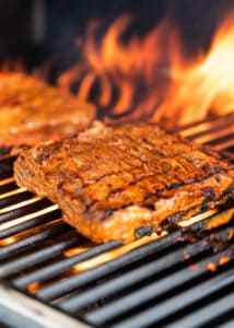 side view: steak on gas grill with flames in background