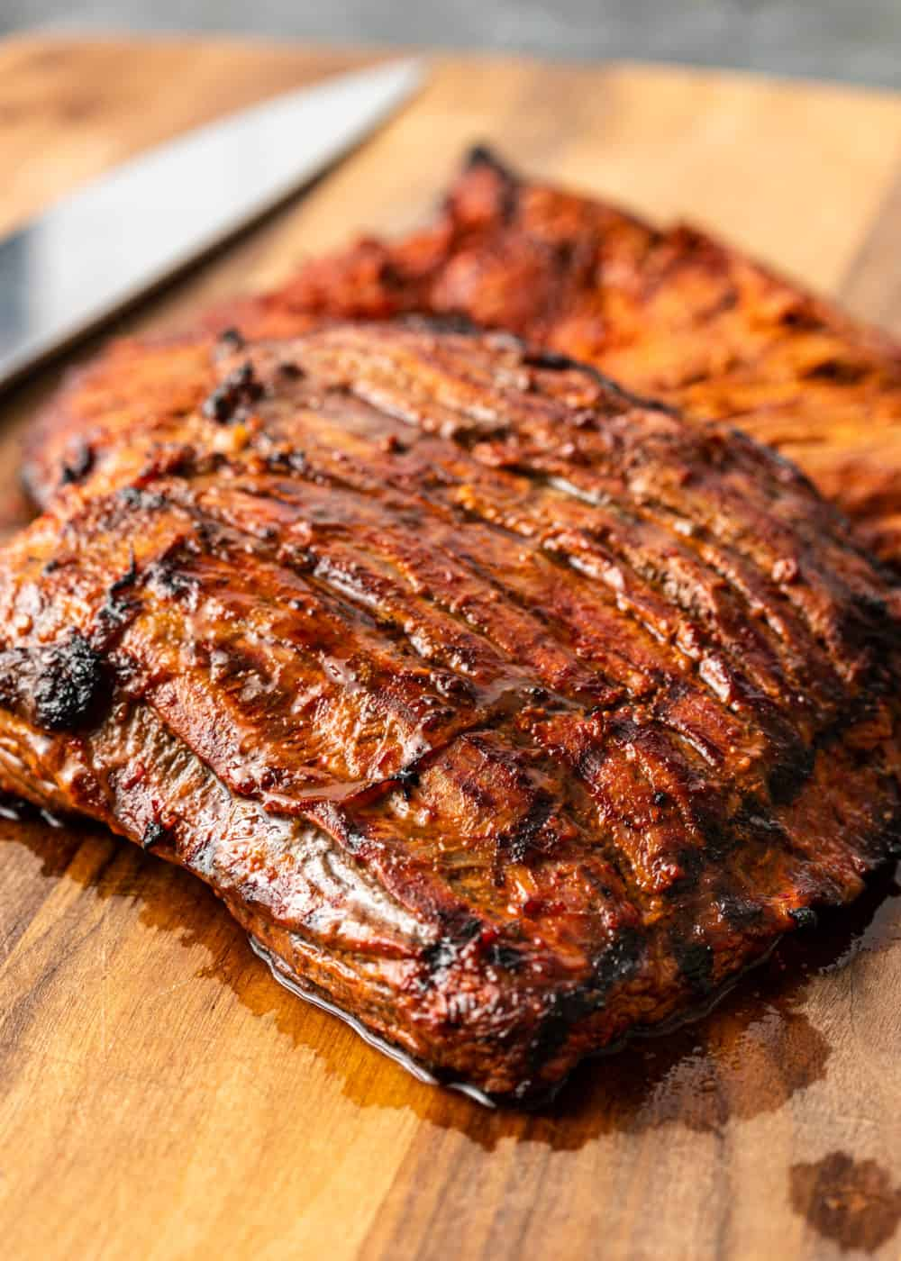 closeup: grilled Mexican steak resting on wooden cutting board