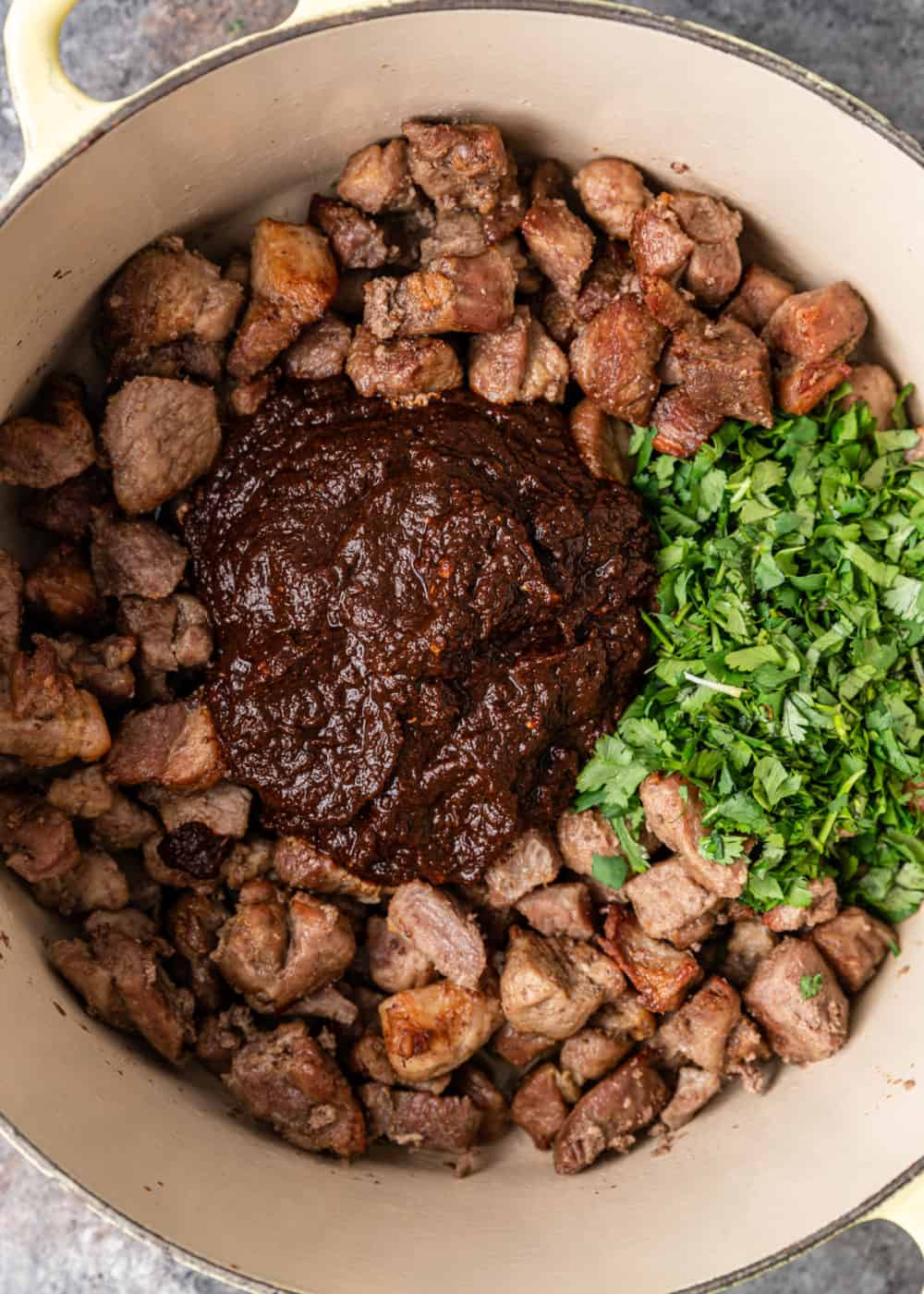 bite size pieces of pork shoulder in large pot with red chile paste and chopped cilantro