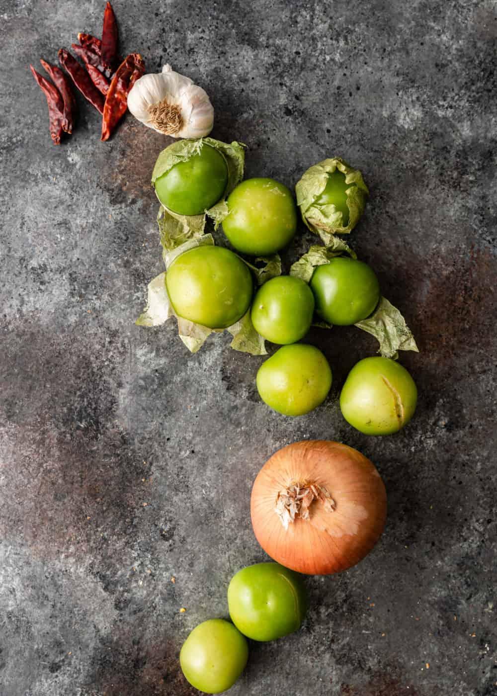 overhead: fresh tomatillos, garlic, onion, and red chili peppers for salsa de tomatillo