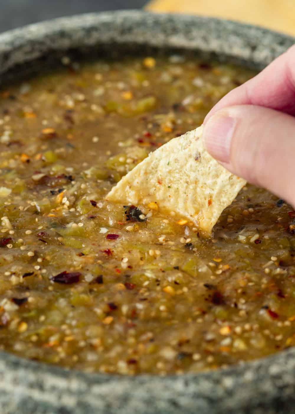 dipping tortilla chip into bowl of spicy tomatillo salsa