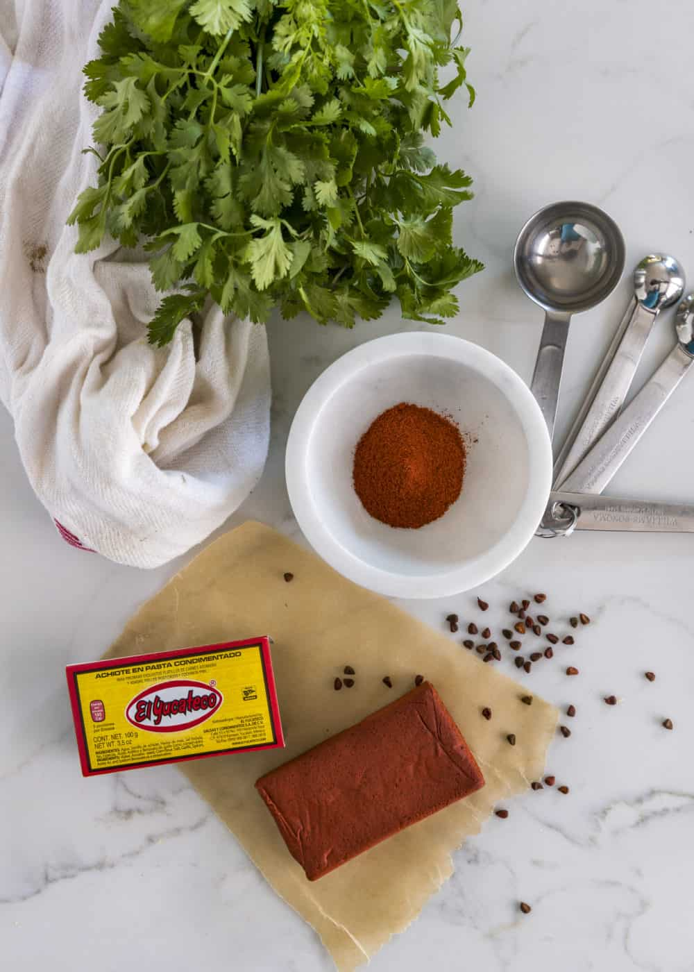 overhead image: block of achiote paste on counter with small bowl of achiote powder and bunch of cilantro