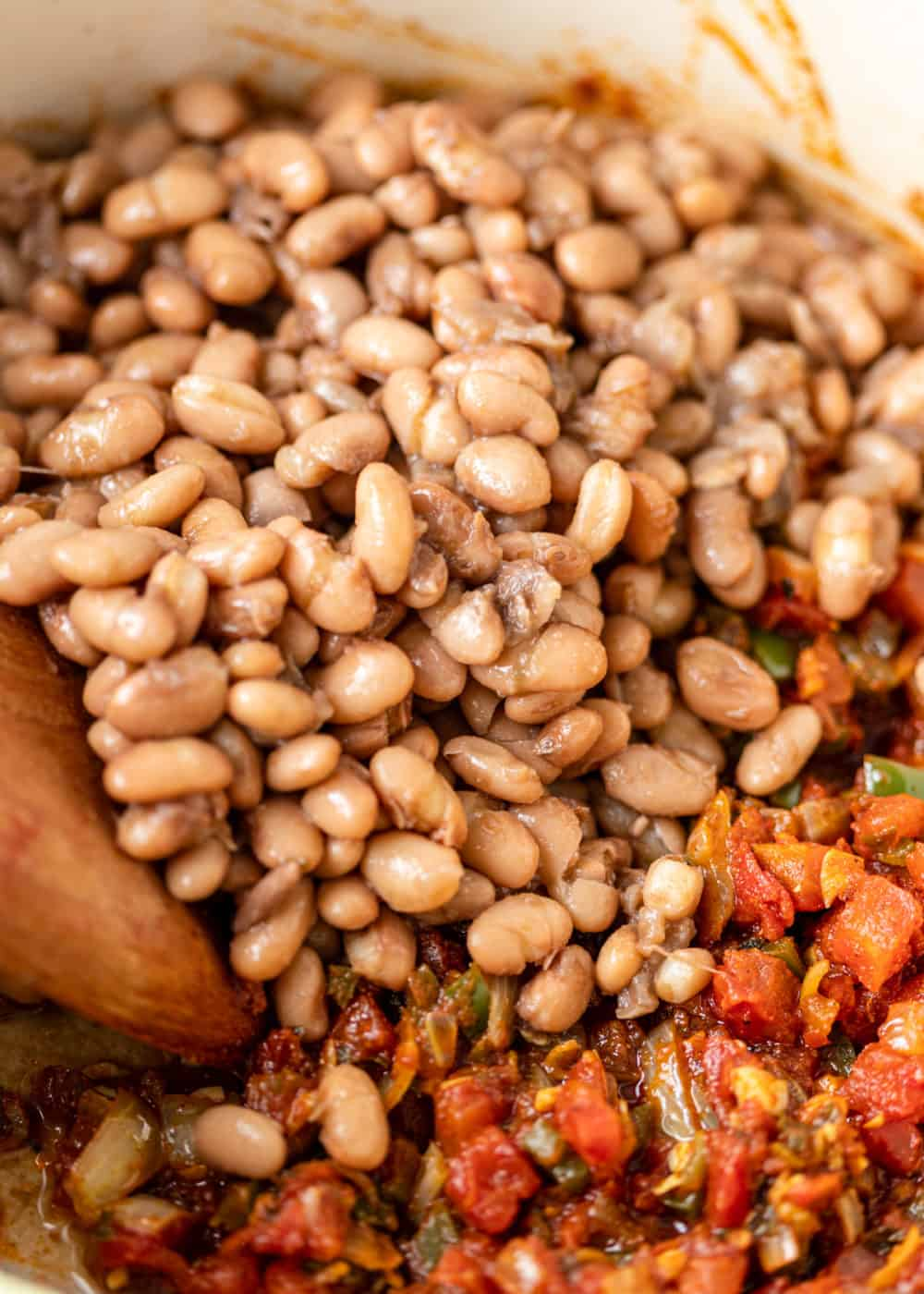 adding cooked pinto beans to spicy tomato mixture in white pot