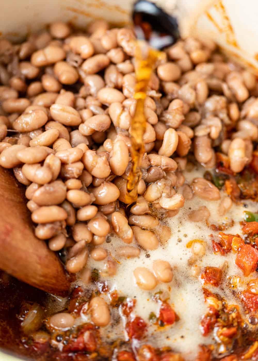 pouring beer into pot to make borracho beans