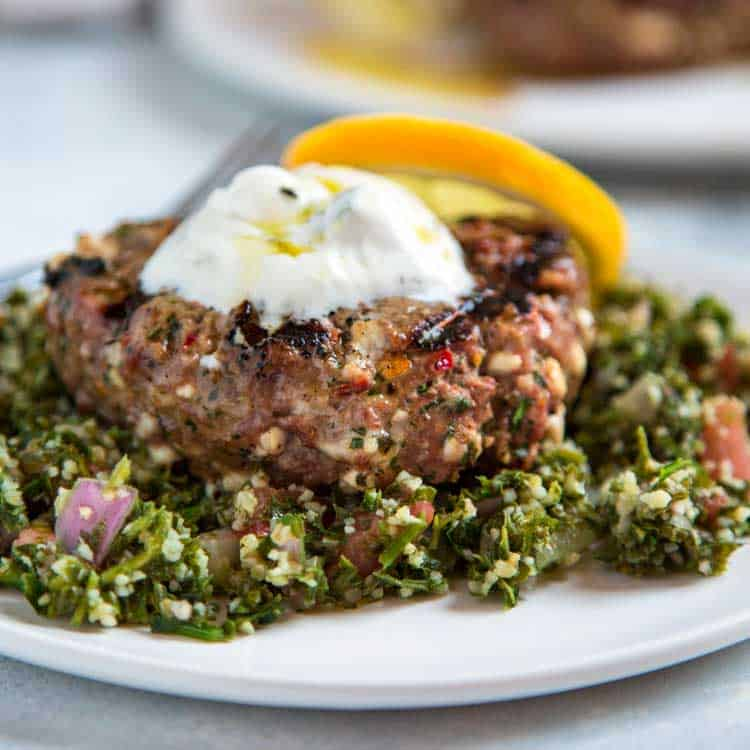 closeup photo of ground lamb burger on plate with fresh herbs