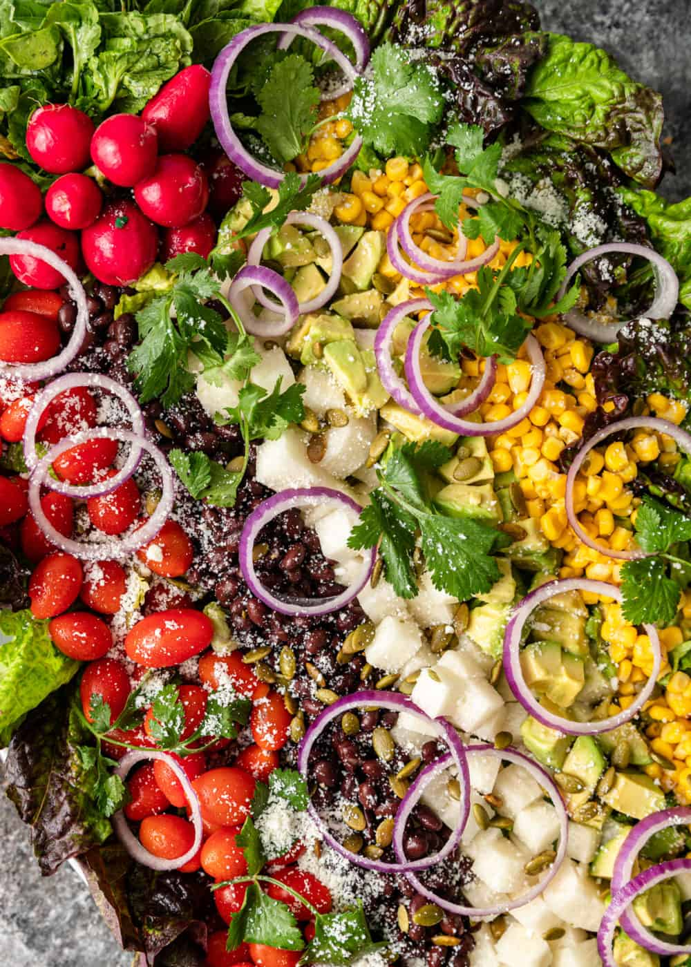 overhead image: close up image of garden vegetable salad topped with black beans, corn, and Cojita cheese