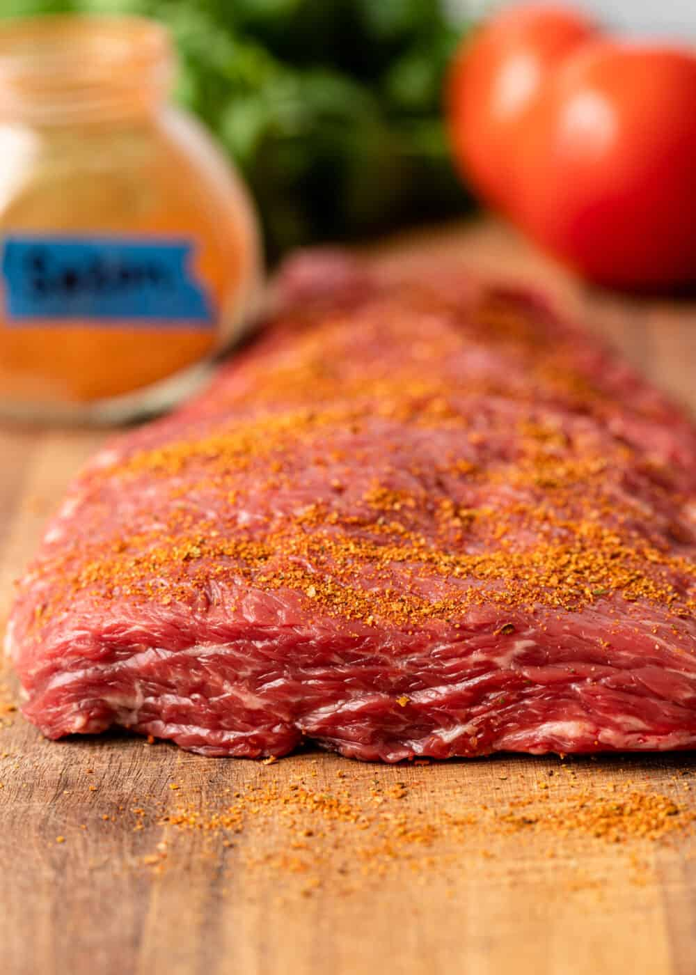 uncooked sirloin flap seasoned with spice rub on butcher block cutting board