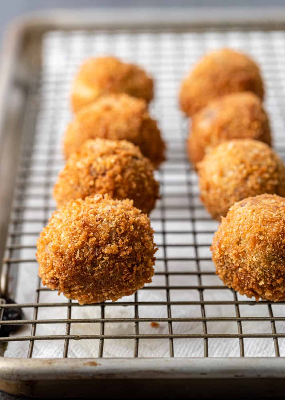 golden brown fried boudin balls on wire rack