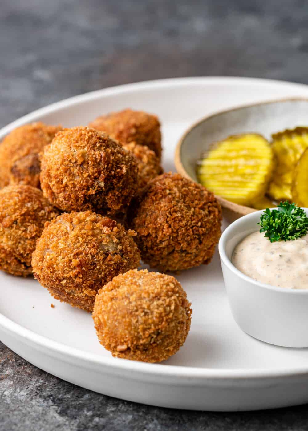 Cajun appetizer of boudin balls on white platter with pickle slices and Cajun remoulade sauce