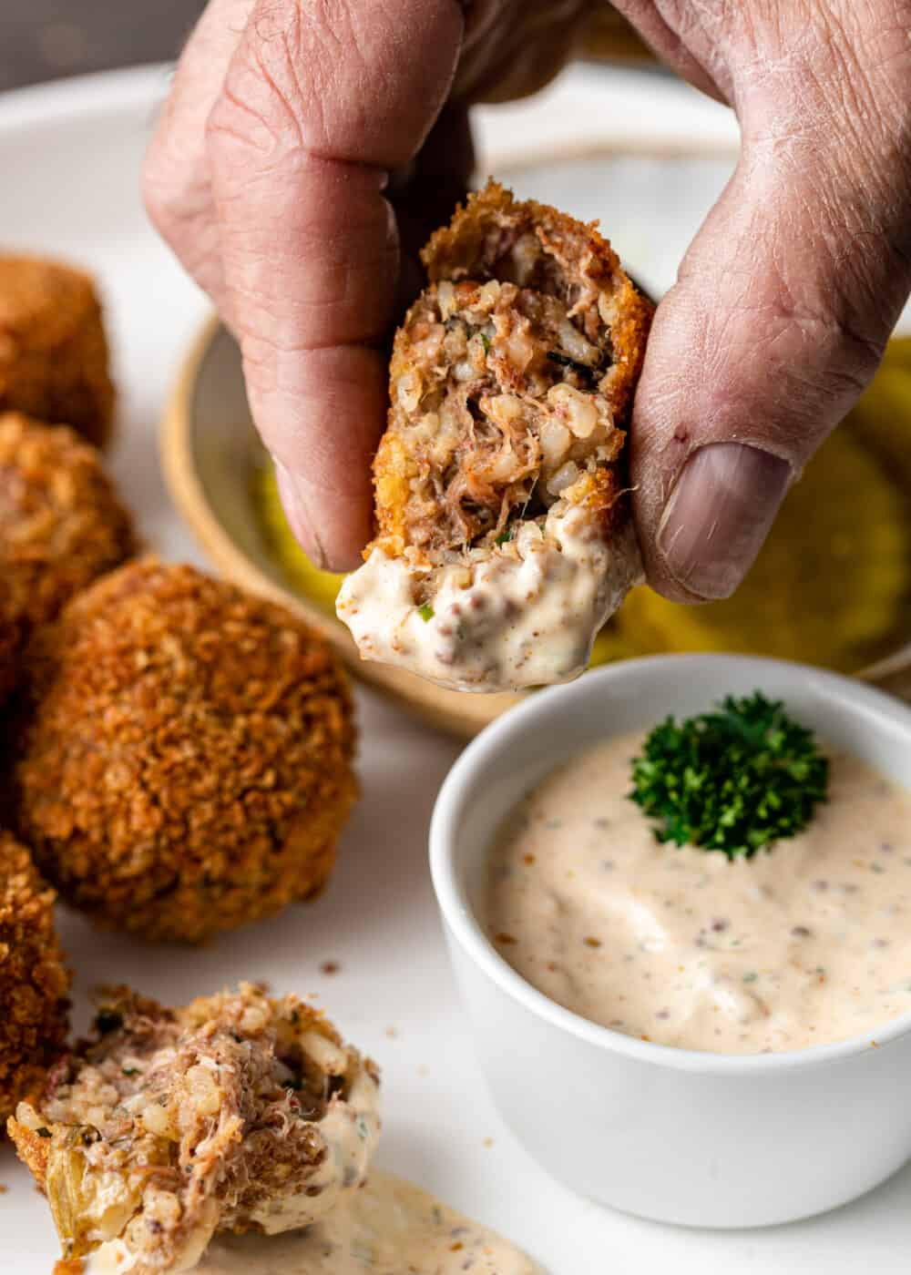 man's hand holding half of a boudin ball that's been dipped in Cajun remoulade