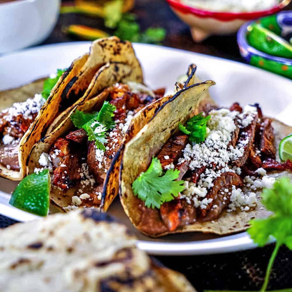 3 carne asada tacos on a white platter