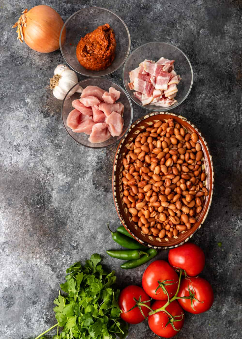 overhead image: bowls of boneless pork, chopped bacon, and other ingredients for a Mexican pinto beans side dish