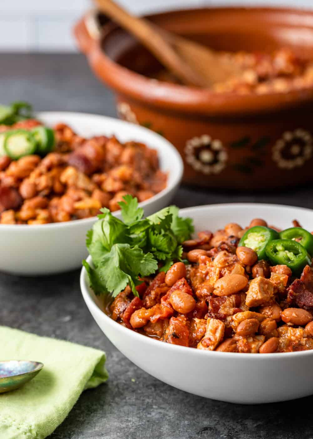 two white bowls of charro beans garnished with cilantro and jalapeno slices