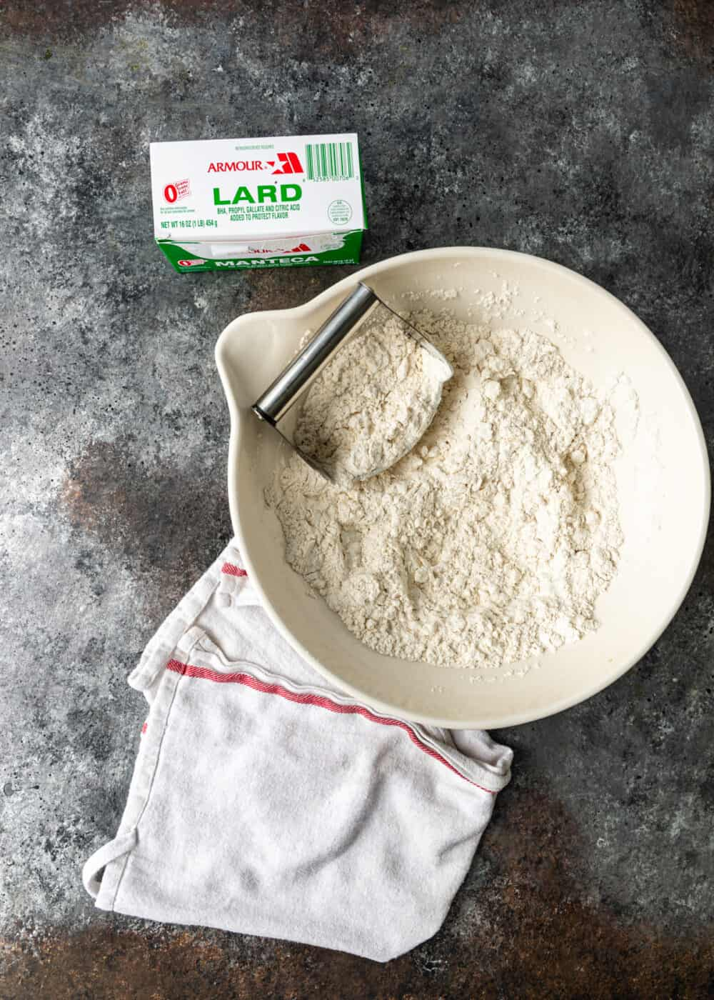 cutting lard into all purpose flour for empanada dough