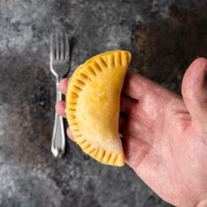 empanada ready for baking in palm of man's hand